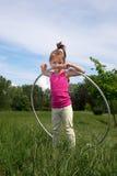 有Hula箍的微笑的小女孩享受美好的春日的在公园 免版税图库摄影