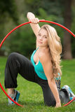 有hula箍的年轻女运动员在公园 库存照片