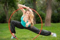 有hula箍的年轻女运动员在公园 库存图片