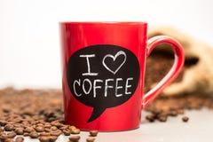 有I爱用白垩做的咖啡标志的红色陶瓷杯子。 免版税库存图片