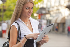 有iPad片剂计算机的妇女在都市街道 库存图片