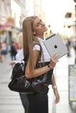 有iPad片剂计算机的妇女走在街道的 图库摄影