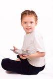 有ipad的微笑的小女孩 免版税库存图片