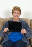 有Ipad计算机的成熟资深年长妇女 免版税图库摄影