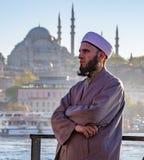 有iPhone的保守的伊斯兰教的人在轮渡和蓝色清真寺 免版税库存照片