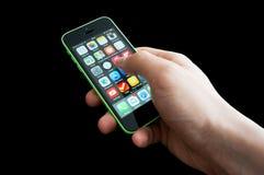 有iphone 5C的家庭屏幕的手 库存图片