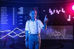 有IT路线和小心地接触一个透明设备的镇静男孩 库存照片