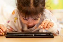 有IV被包扎的解答演奏数字片剂放松,当停留时的病的亚裔小孩女孩 免版税图库摄影