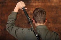 有katana剑的人在棕色蜡染布背景 免版税图库摄影