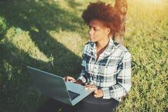 有laptopn的两种人种的女孩在公园 库存图片