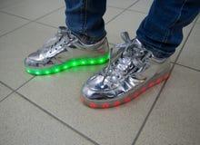 有LED照明设备的时兴的运动鞋在一个人的腿 免版税库存照片