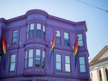 有LGBT自豪感彩虹旗子垂悬的紫色房子 免版税库存图片
