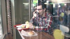 有LGBT镯子标志的一个人,在咖啡馆坐并且使用电话 影视素材