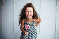 有lollypop的滑稽的卷曲女孩 免版税库存图片