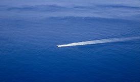 有lond苏醒足迹的快艇后边在完善的蓝色海 库存图片