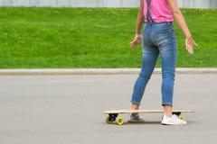 有longboard特写镜头的女性腿 女孩在委员会准备乘坐 对拷贝空间 免版税库存图片