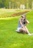 有Longboard的微笑的白种人白肤金发的十几岁的女孩在绿色夏天公园 免版税库存图片