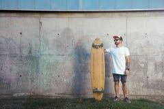 有longboard的被刺字的人在一个混凝土墙旁边 免版税库存图片