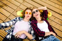 有longboards的两个时髦的年轻都市女孩在街道的木地板说谎 朋友获得乐趣并且花费时间 免版税库存图片