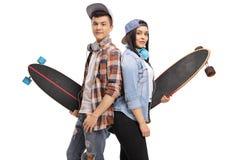 有longboards的少年溜冰者与他们的反对每ot的后面 免版税库存图片