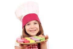 有macarons的小女孩厨师 免版税图库摄影