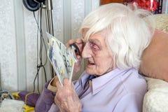 有magnifyer寸镜的年长视觉减弱的妇女 免版税库存图片