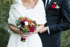 有marsala钮扣眼上插的花的有红色玫瑰花束的新郎和新娘 库存照片