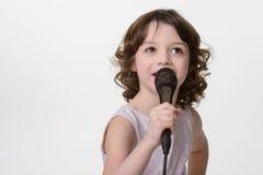 有mic的唱歌的可爱的女孩 免版税库存照片