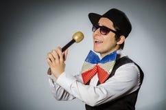 有mic的滑稽的人在卡拉OK演唱概念 库存照片