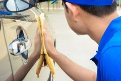 有microfiber布料的一辆人清洁汽车 免版税库存照片