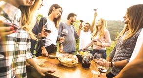 有Millenial的朋友乐趣时间饮用的红酒oudoors -享受收获的愉快的花梢人民在农舍葡萄园酿酒厂- 图库摄影