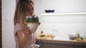 有mojito玻璃的年轻女人在她的拿着鸡尾酒饮料的手特写镜头的 影视素材
