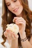 有moneybox的可爱的女孩 免版税库存图片