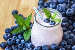 有nat水多的新鲜的莓果背景顶视图酸奶的鸡尾酒的美丽的开胃菜蓝莓果子圆滑的人奶昔玻璃瓶子 免版税库存照片