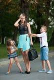 有naughti儿子adn女儿的母亲步行的在公园 免版税库存照片