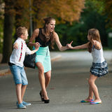 有naughti儿子adn女儿的母亲步行的在公园 免版税库存图片