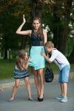 有naughti儿子adn女儿的母亲步行的在公园 图库摄影