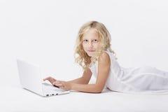 有netbook的,白色背景美丽的白肤金发的小女孩 免版税库存照片