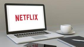 有Netflix商标的膝上型计算机在屏幕上 现代工作场所概念性社论3D翻译 皇族释放例证
