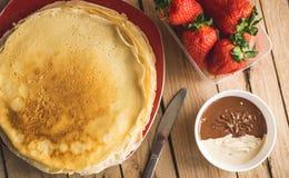 有nutella和草莓的绉纱 背景土气木 免版税图库摄影