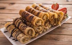有nutella和草莓的绉纱 背景土气木 免版税库存图片
