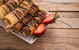 有nutella和草莓的绉纱 背景土气木 图库摄影