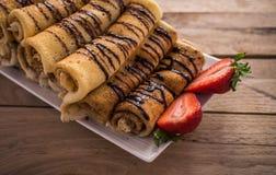 有nutella和草莓的绉纱 背景土气木 免版税库存照片