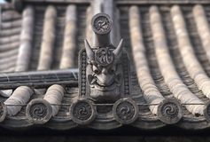 有onigawara gargoyl的日本传统古色古香的陶瓷屋顶 免版税库存图片
