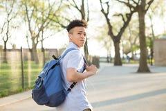 有packpack步行的年轻西班牙男孩在学院校园里 库存图片