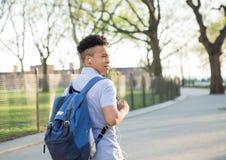 有packpack步行的年轻西班牙男孩在学院校园里 图库摄影