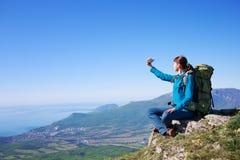 有packpack的年轻女性旅行家在山lanscape做 图库摄影