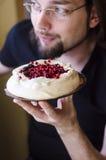 有pavlova蛋糕的愉快的人 免版税图库摄影
