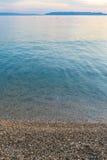 有Pebble海滩和土地的镇静干净的海天际的 库存照片