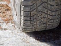 有peebles的冬天轮胎在充分一条肮脏的路的凹线  免版税库存照片